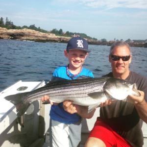 young man holding his catch with the captain
