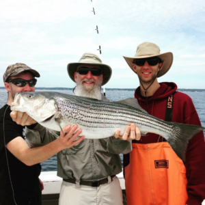 Grandfather and Grandsons holding striped bass